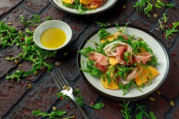 Fresh Tasty Persimmon salad with arugula, parma ham, olive oil, pumpkin seeds and herbs. autumn, winter healthy food