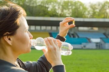 Outdoor portrait of mature woman taking vitamin E