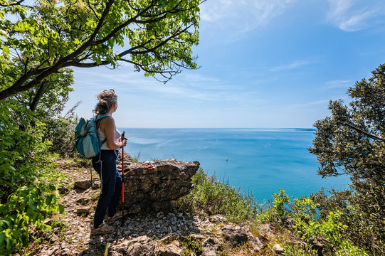 Mature hiker looking the sea. Travel and active lifestyle concept.