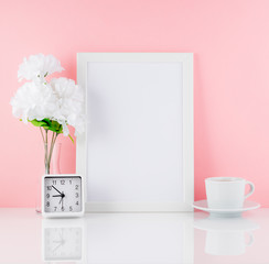 Blank white frame, flower, clock, cup of coffee or tea on a white table against the pink wall with copy space. Mock up.