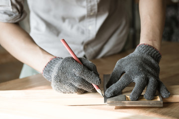 carpenter measuring and writing on wood with copy space background