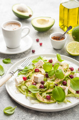 Avocado salad with olive oil, feta cheese, lime, cranberries, basil leaves and dressing with spices with cup of coffee on the table.