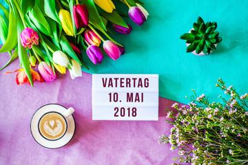 Vatertag Mai auf lightbox mit bunten Blumen als flat lay