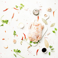 Raw whole chicken with spices and marinade, gray background, top view