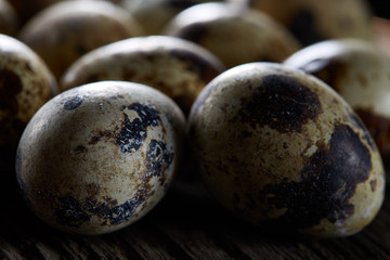 Spotted quail eggs arranged on the background of old wooden boards, with copy-space, selective focus.