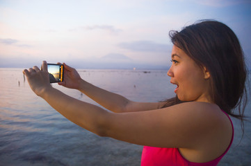 young woman with mobile phone camera taking picture of beautiful beach sunset landscape and mount Agung volcano of Bali in Asia holidays travel