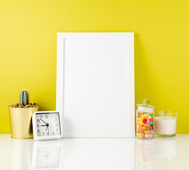Blank white frame, clock, succulent, candy on a white table against the yelloow wall. Mockup with copy space.