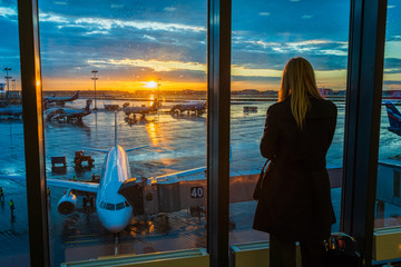 Woman is standing by the window at the airport on sunset background