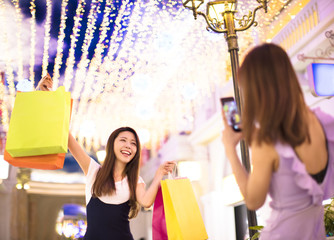 happy woman showing shopping bags in mall