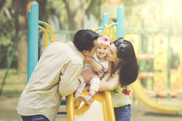 Father and mother kissing daughter on slides