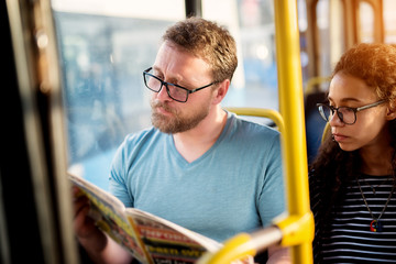 A young adorable couple is sitting together on a bus seat and reading newspapers as they wait for their destination.