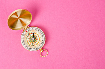 Vintage gold compass on pink paper