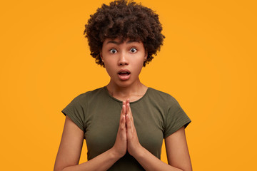 Shocked beautiful African American female feels worried and excited, presses palms together, being terrified with something, poses against yellow background. People and surprisement concept.