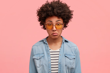 Hesitant discontent female curves lips with uncertainty, looks in bewilderment at camera, wears stylish yellow shades, isolated on pink studio background. People, facial expressions concept.