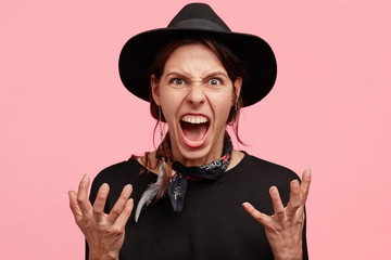 Portrait of irritated young cowgirl gestures angrily, shows annoynace, being mad and crazy, yells with negativity, opens mouth widely, wears black stylish clothes, isolated over pink background