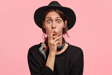 Indoor shot of thoughtful surprised female in cowboy clothes, keeps fingers on lips, eyes popped out, feels excited as hears uexpected news, isolated over pink background. Facial expressions concept