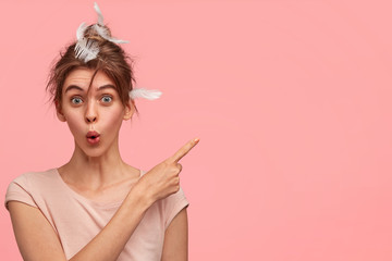 Shocked female with feathers on head, just woke up after healthy sleep, has mess on head, indicates at blank copy space, advertises something for rest or things in bedroom, poses on pink wall