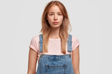 Wall Mural - Horizontal shot of good looking Caucasian female with long hair, dressed in stylish overalls, looks directly at camera, ready for walk outdoor and spending weekends with friends, models in studio