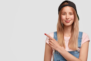 Wall Mural - Happy female youngster in trendy black cap and denim overalls, has delighted expression, lovely appearance, indicates at blank copy space for your advertisement or promotional text. Look there
