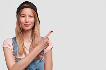 Wall Mural - Hipster female in stylish cap and jean dungarees, advertises new stylish outfit for youth, points with fore finger at blank space for your text. Fashionable teenager isolated over white background