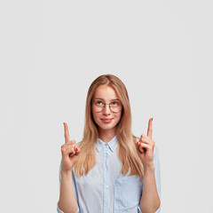 Wall Mural - Beautiful young Caucasian female model indicates at blank copy space for your promotional text or advertisement, wears glasses and shirt, poses against white background. Look upwards, please