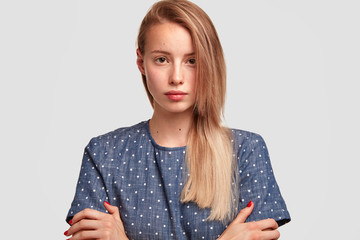 Serious European woman looks directly at camera, keeps hands crossed, has long hair, wears fashionable blouse, isolated on white background. Attractive young college student comes to classes
