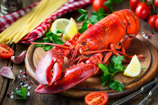 Steamed red lobster on a wooden cutting board with parsley, lemon wedges and spaghetti at the background. Spaghetti all'astice or Lobster spaghetti recipe