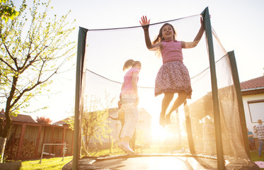 Three charming cute kids are jumping on the trampoline and the youngest girl is attempting to jump over the safety net during a beautiful sunny day.