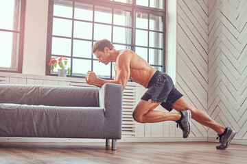 Handsome shirtless muscular male does exercise leaning on a sofa at home.