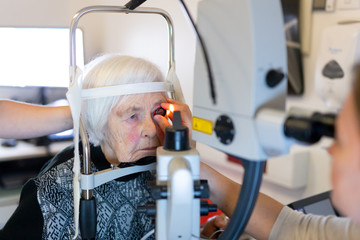 Elderly 95 years old woman during laser surgery at ophthalmology clinic. Senior woman face and eye with laser light. Age, vision, surgery, eyesight and people concept.