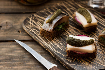 Mini sandwiches with bacon and herring as a snack to vodka on a dark background