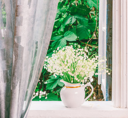 bouquet of Lily of the valley flowers on the windowsill in a rustic house in the spring morning