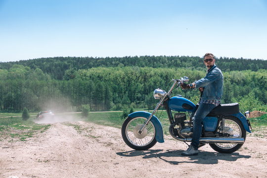 Portrait young guy with sunglasses and Jeans jacket and pants posing sitting on his vintage retro motorbike. biker wearing jeans, fashion men. old timer age concept, 1960s style, outdoor dirt road