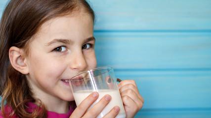 Cute little girl enjoys the taste of fresh milk