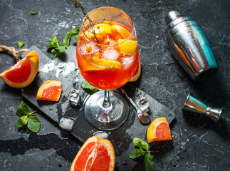 Cocktail drink on stone board. Alcoholic beverage with grapefruit and ice
