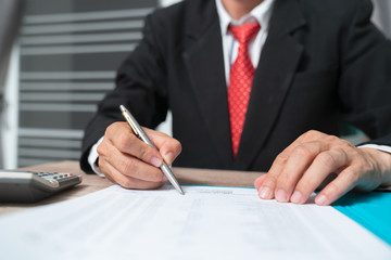 Hand of businessman writing on paper in office
