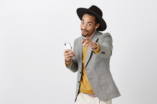 This song is about you. Portrait of charming dark-skinned stylish student in hat and trendy outfit holding smartphone, listening music in earphones and dancing, pointing at camera as if flirting