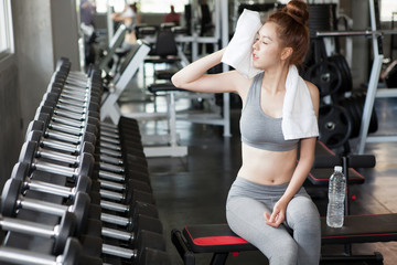 Beautiful fit young woman with white towel over his shoulder sitting on a bench and Bottle water after exercise in fitness gym .  Tired sport girl resting after training wiping sweat