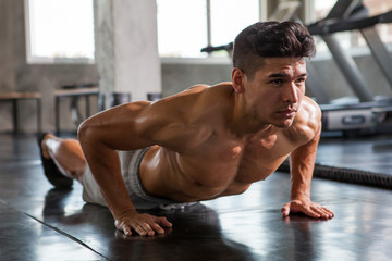 Muscular bodybuilder guy doing push ups exercise  in fitness gym . Shirtless young sport man training
