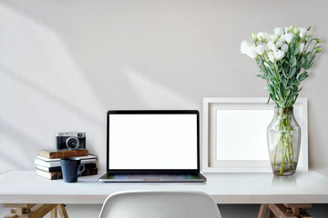 Stylish workspace with laptop computer and mockup poster on home or studio.