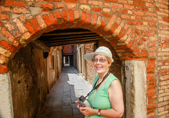 Happy mature tourist woman travelling in Italy stays against narrow street and arch in Venice.