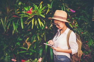 girl play the tablet  tourist travel in flower garden, Travel concept.