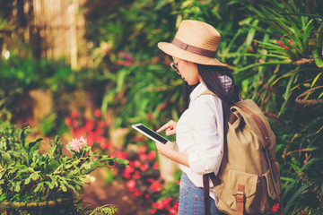 girl play the tablet  tourist travel in flower garden, Travel concept.