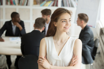 Attractive female team leader looking to side, hands crossed, colleagues discussing project ideas, results at background, analyzing report, predicting financial trends. Big expectations, achievements