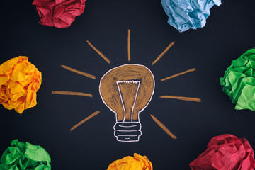 Drawing of a light bulb and colourful crumpled paper balls