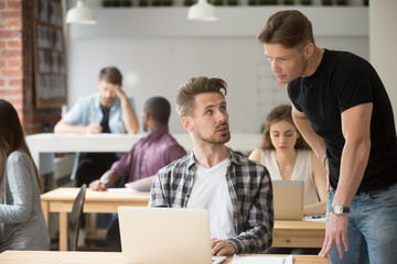 Male intern asking for help from experienced supervisor showing problem on laptop in coworking office space. Two male colleagues consulting and negotiating on work issues. Concept of help, cooperation