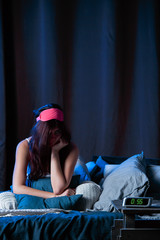 Image of young brunette with insomnia with pink bandage for eyes sitting on bed next to clock
