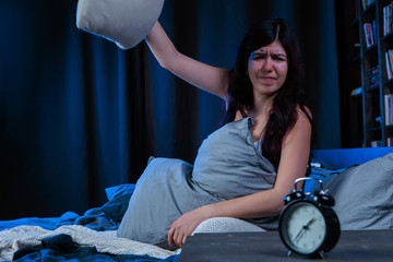 Photo of dissatisfied woman with insomnia throws pillow sitting on bed next to alarm clock