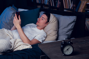 Photo of man with sleeplessness with phone in hands lying in bed next to alarm clock