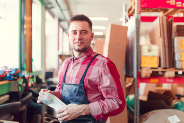 Image of man in apron with bag in hands at shop for making coffee
